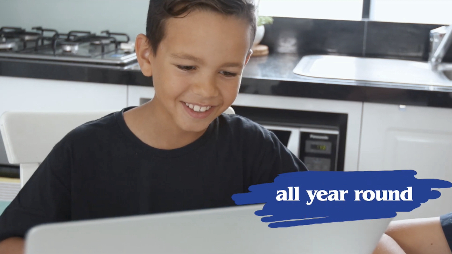 Boy smiling while he works on his computer from home