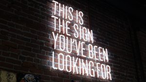 Neon sign on a brick wall that says THIS IS THE SIGN YOU'VE BEEN LOOKING FOR